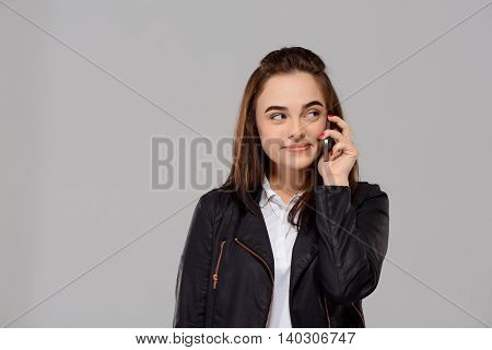 Young beautiful girl speaking on phone, smiling over purple background. Copy space.