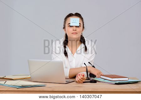 Young beautiful businesswoman looking at camera, sitting with sticker on forehead at workplace over purple background. Copy space.
