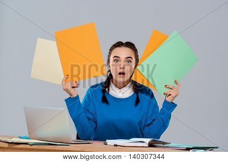 Surprised young beautiful businesswoman sitting at workplace, holding colorful folders, looking at camera over purple background. Copy space.