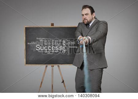 Businessman pulling rope with blackboard - studio shot