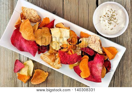 Plate Of Colorful Organic Vegetable Chips With Dip Downward View On Rustic Wood