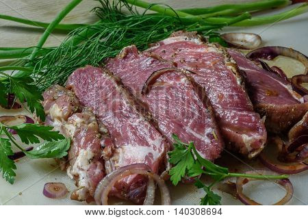 chunk of meat marinated in chili sauce with onion and herbs, sliced steak and ready for frying