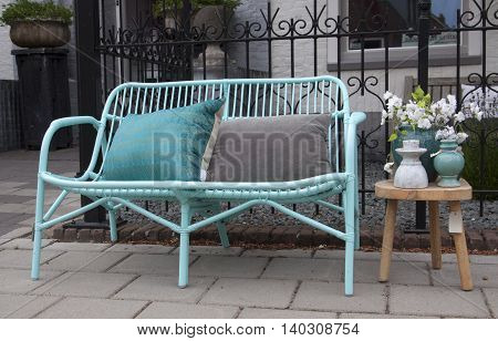 Vintage bamboo chair or sofa and pillows with pastel colors and still life on a garden table.
