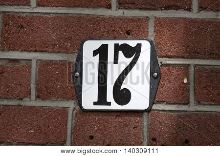 Enameled house number seventeen on a red brick wall