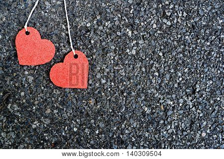 two red hearts placed on black pavement