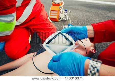 Electrodes of the defibrillator. Rescue team (doctor and a paramedic) resuscitating the man on the street.