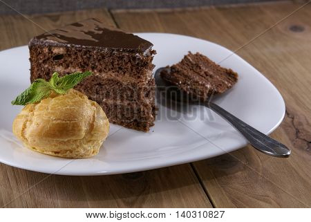 Dessert on a plate on a rustic wooden table: profiterole, decorated with mint leaves and a slice of chocolate cake
