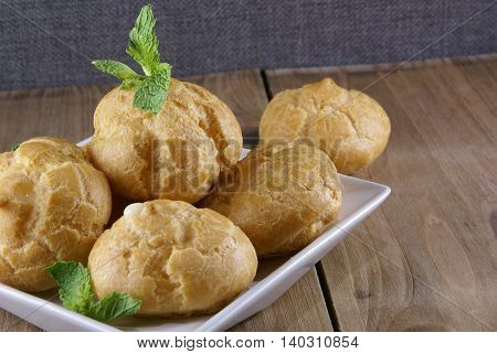 Cakes profiteroles decorated with mint leaves lying on a rustic wooden table