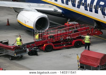 HAMBURG; GERMANY; JULY 27 2016: Aircraft of Ryanair and discharging of the passengers luggage at the gate in the terminal in the international airport Hamburg Fuhlsbüttel Germany's oldest and fifth largest airport