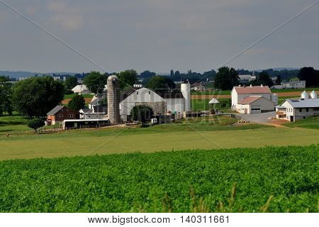 Lancaster County Pennsylvania - June 6 2015: A large Amish farm with fields of crops barns silos sheds and family home