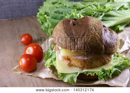 Picnic, sandwich with meat, cheese and fresh vegetables is lying on a rustic wooden table.