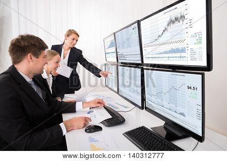 Happy Young Stock Market Brokers Looking At Graphs On Multiple Computer In Office