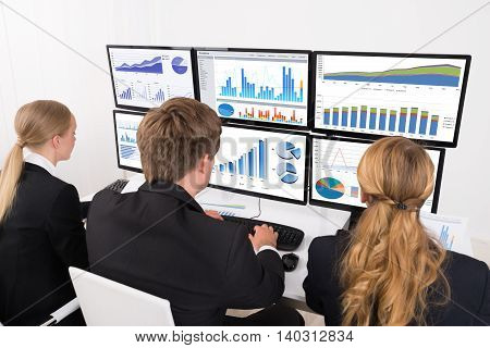 Young Male And Female Businesspeople Looking At Financial Graphs On Multiple Computers In Office
