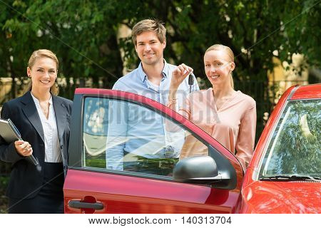 Dealer Standing Besides Happy Young Couple With Key Of Newly Purchased Car