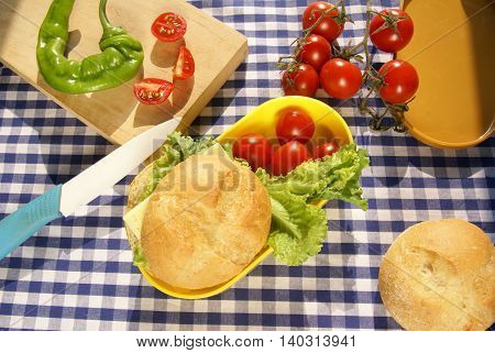 Cooking lunchbox. Yellow box lunch sandwich with cheese and a knife lying on a cutting board, fresh vegetables (pepper, tomatoes, lettuce)