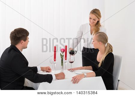Female Waitress Pouring Red Wine Into Wineglass For Young Couple In Restaurant