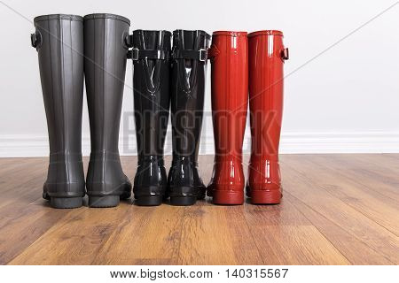 Women's and Men's Rubber Boots on Laminated Flooring