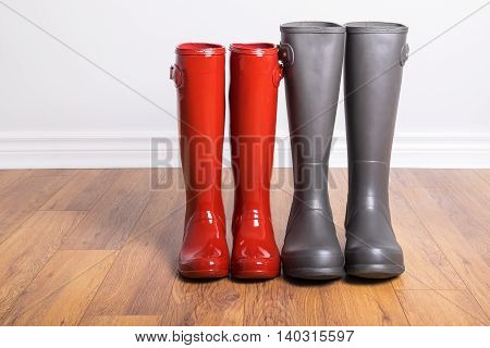 Women's and Men's Rubber Boots On Laminated Floor