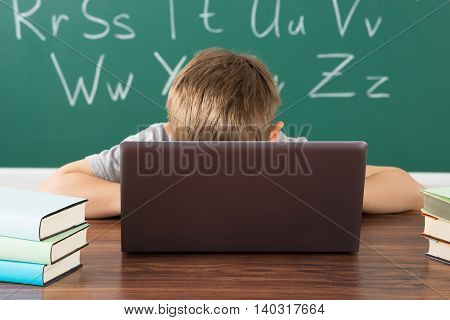 Little Boy In Classroom With Laptop And Stack Of Books On Desk