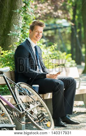 Young Male Businessman Sitting On Bench Using Mobile Phone At Park