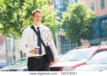 Portrait Of Happy Young Businessman With Disposal Cup