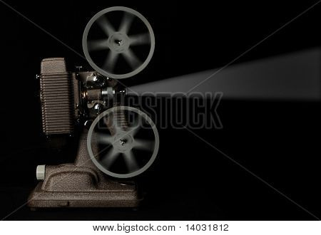 vintage movie projector running against dark background