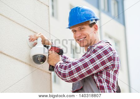 Young Male Technician Installing Camera On Wall Using Electric Cordless Drill