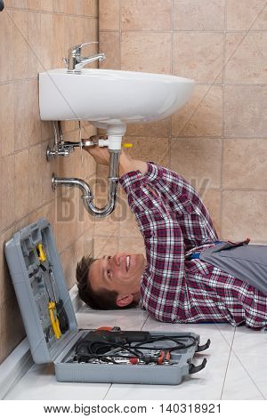 Happy Young Male Plumber Lying On Floor Fixing Sink In Bathroom