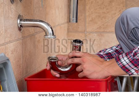 Close-up Of Plumber's Hand Fixing Sink In Bathroom