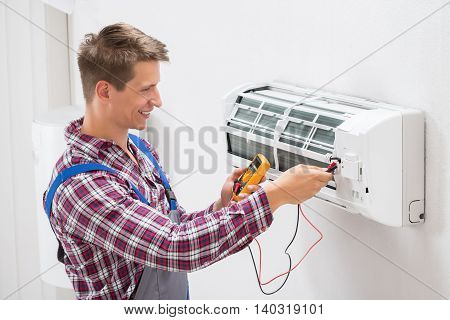 Male Technician Examining Air Conditioner With Multimeter