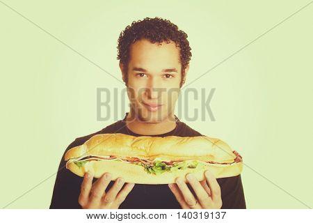 Man holding large sub sandwich