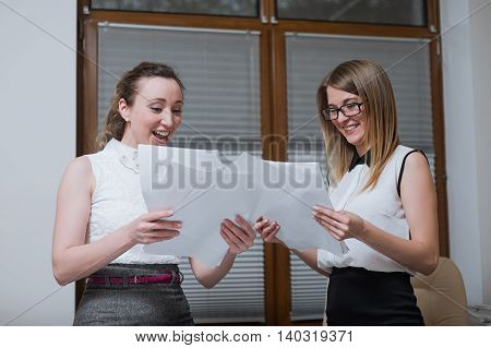 Two Women Business Partners Look On Financial Statements, Statistics And Documents