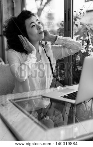 Asian girl sitting at a table in a cafe with a laptop, in headphones to enjoy music. Black and white photo.