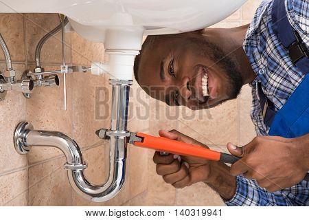 Close-up Of Happy Young African Male Plumber Repairing Sink In Bathroom