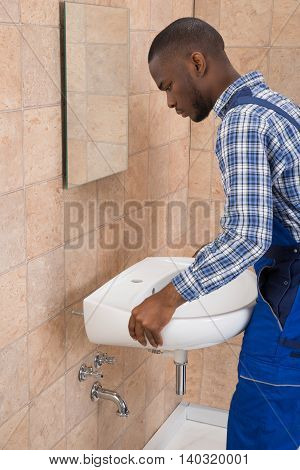 Side View Of Young African Male Plumber Fixing Sink In Bathroom