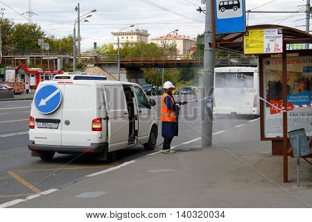 Russia Moscow - August 15 2015: Worker with water hose washes the light post at the bus stop in Moscow
