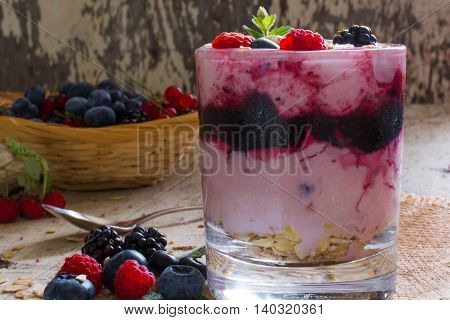diet dessert with yogurt oat flakes fresh berries jam and wicker bowl full of ripe berries on white rustic wooden background. close-up