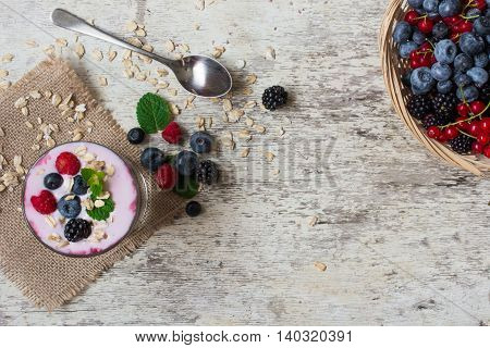berry smoothie with oatmeal mint and spoon in a glass standing on canvas on white rustic wooden background with wicker bowl full of ripe wild berries. top view