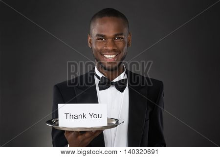 Young Happy African Waiter Showing Thank You Card In Tray