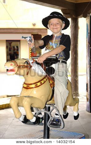 6 year old boy wearing cowboy attire riding a vending machine pony