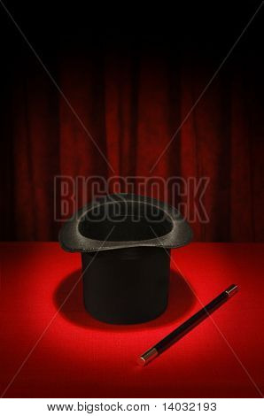 Magician's top hat and magic wand in spotlight on red table cloth and red draped background
