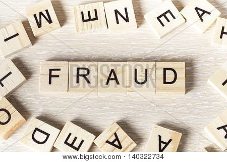 fraud word written on wood block. Wooden ABc.
