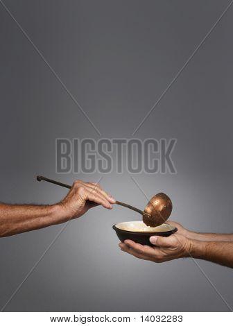 Mann, hält eine Schüssel in beide Hände, empfangen eine Portion Suppe aus einem anderen Mann, hält eine Suppenkelle