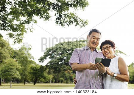 Senior Couple Cheerful Earphones Mobile Concept