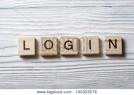 LOGIN word written on wood block at wooden background.