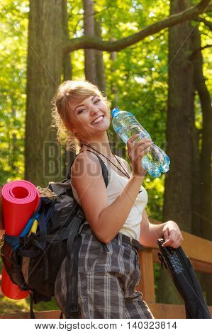Adventure tourism enjoying summer time - young tourist hiker woman with backpack water bottle in forest trail