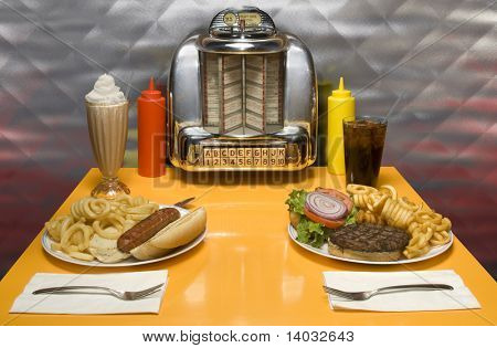 1950's style diner table with juke box, malt, cola, hot dog and hamburger.