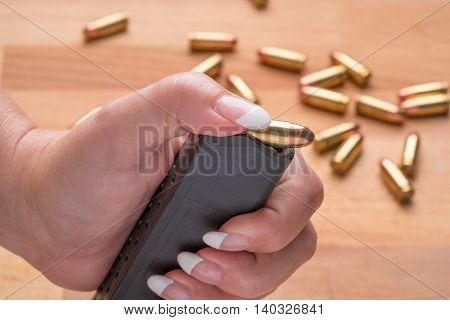 Woman Loading 9mm Ammunition in High Capacity Handgun Magazine on wood Surface