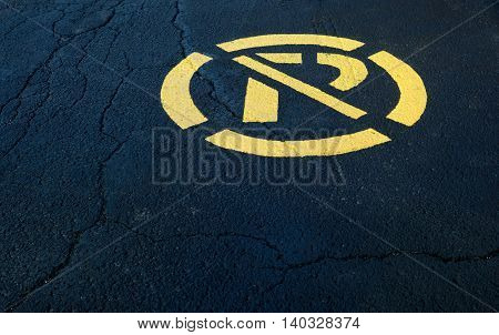 no parking sign painted in yellow on black asphalt