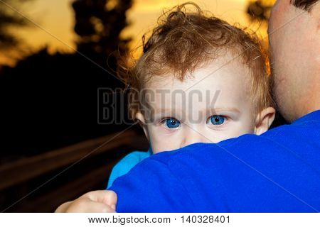 A curly headed baby boy peers over the shoulder of his dad. He has big blue eyes that match the shirt of his father. The sun is setting.